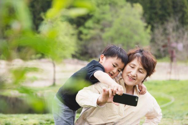 Avó e neto que tomam um selfie no parque - foto de acervo