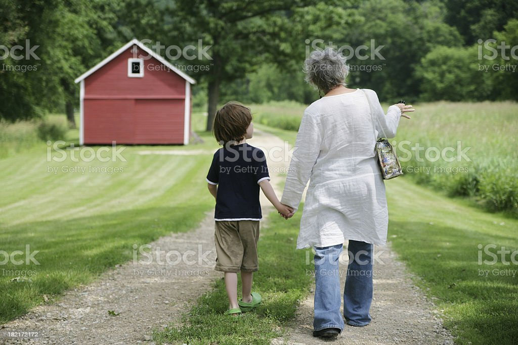Grandmother and Grandson Taking  Walk on Beautiful Trail- Red Barn royalty-free stock photo
