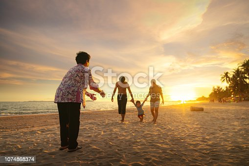 Grandmother and her family play togather on the beach, Phuket beach, Thailand
