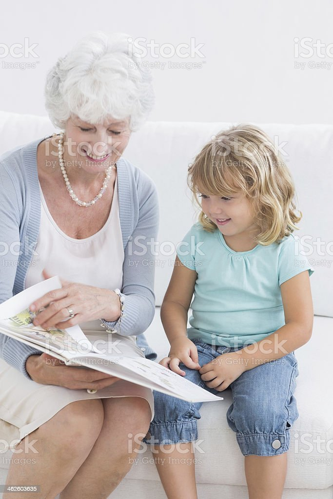 Grandmother and her granddaughter reading a storybook royalty-free stock photo