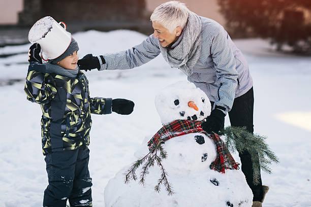 grandmother and her grandson making snowman - schneespiele stock-fotos und bilder