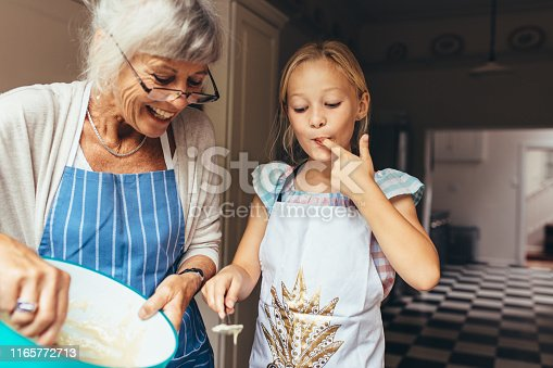 istock Grandmother and kid having fun making cake in kitchen 1165772713