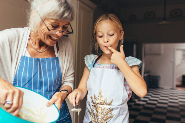 Grandmother and kid having fun making cake in kitchen Senior woman in apron making batter for cake. Little girl tasting cake batter standing in kitchen with grandmother. granddaughter stock pictures, royalty-free photos & images