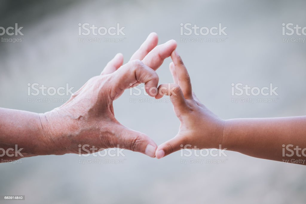 Grandmother and kid little girl making heart shape with hands together stock photo