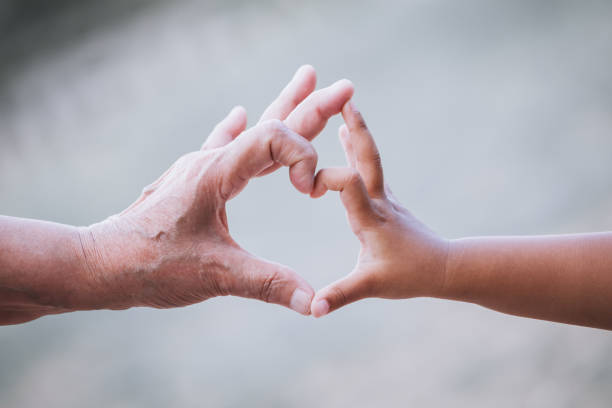 Grandmother and kid little girl making heart shape with hands together - foto stock
