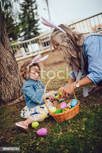 Grandmother and granddaughter having fun with surprise Easter eggs from Easter egg hunt in garden