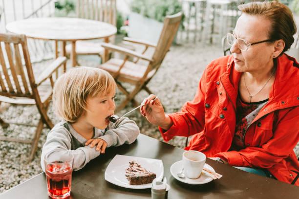 Großmutter und kleine Kleinkind Junge verbringen Zeit zusammen im Outdoor-Café, Essen Schokoladenkuchen, Familienbeziehungen – Foto
