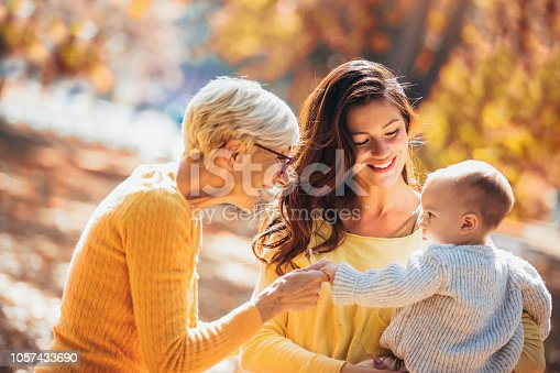 istock Grandmother and mother smiling at baby in autumn park. 1057433690