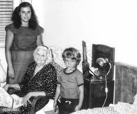 Grandmother and nephews inside bedroom in 1970. The Grandmother is sitting on armchair and the nephews are standing close to her. Some skratches and grain due to the age of the photo. Scanned black and white print.