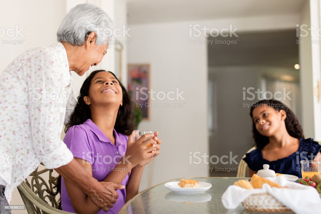 Grandmother and teen granddaughters enjoying snack time - Royalty-free 12-13 Years Stock Photo