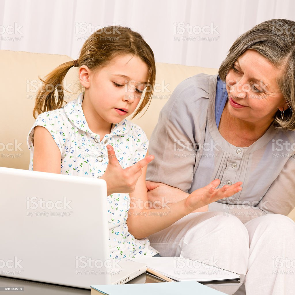 Grandmother and young girl with laptop learn count royalty-free stock photo