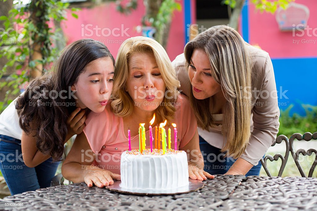 Grandmother Blowing Out Her Birthday Candles Stock Photo More