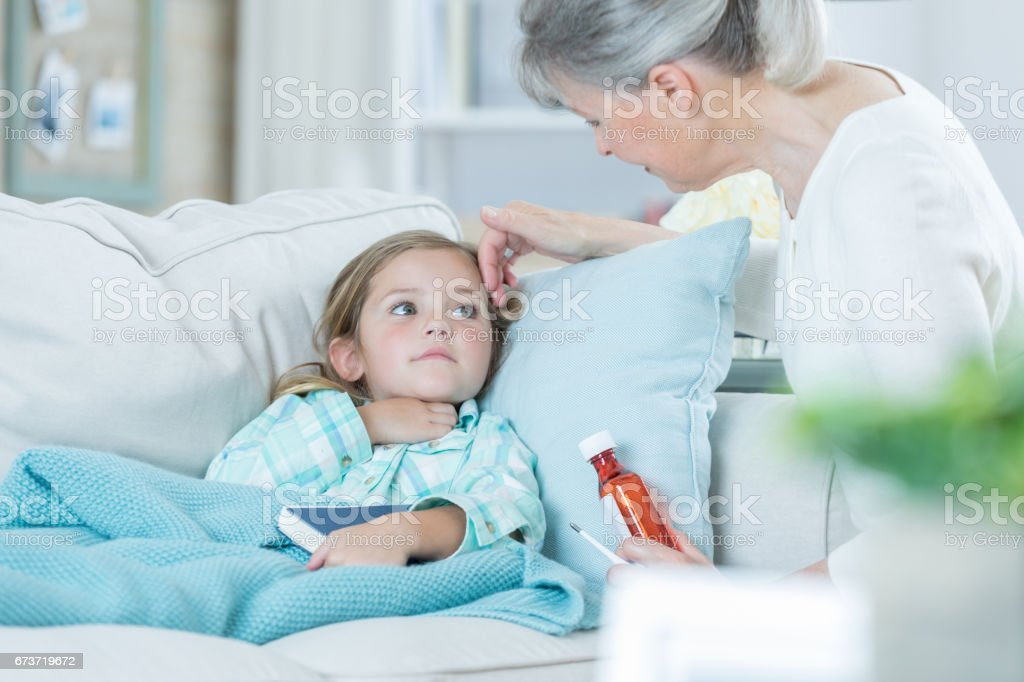 Grandmother cares for sick grandchild stock photo
