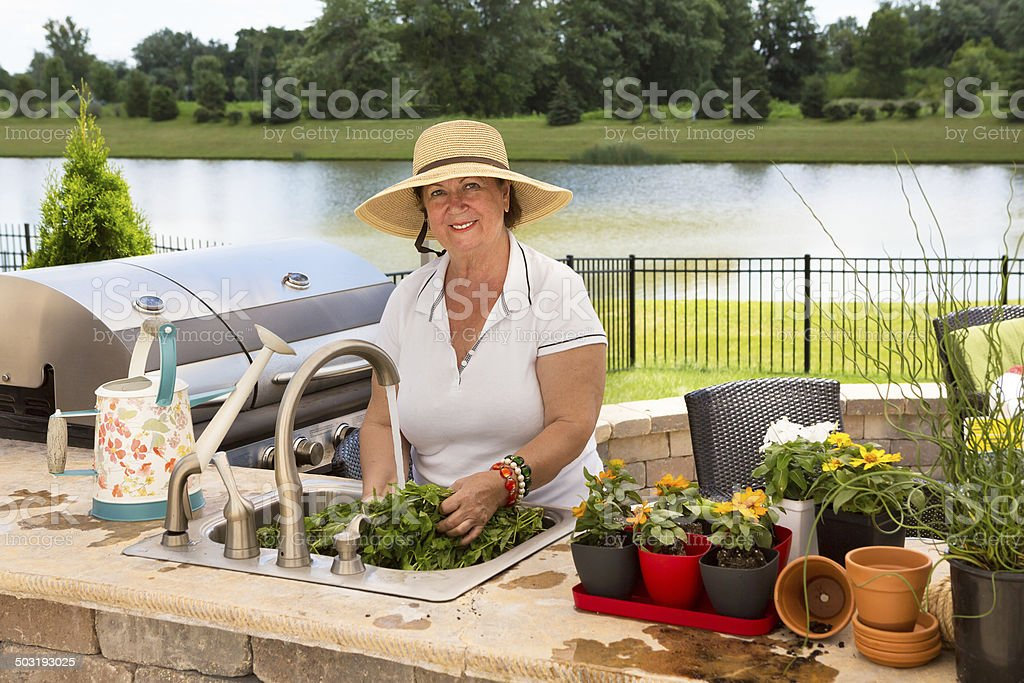Grandmother caring for her potted plants stock photo