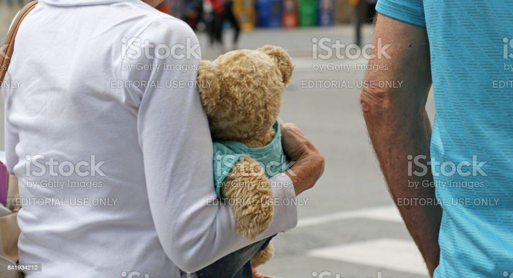 Grandmother Carries Teddy Bear Through Downtown Toronto, Canada stock photo