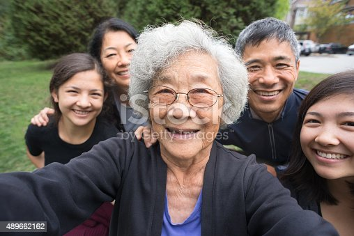 A fit ,senior, Asian Grandmother smiles with her children and mixed-ethnic grandchildren while posing for a selfie in a park garden.   Real, three generation family including a senior woman, mature adult son and daughter and teenage grand-daughters.  An assisted living facility can be seen in the background.  Camera point of view.