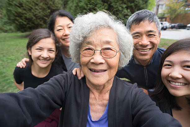 Grandmother, Children, Grandchildren Pose for Selfie, Care Home in Background A fit ,senior, Asian Grandmother smiles with her children and mixed-ethnic grandchildren while posing for a selfie in a park garden.   Real, three generation family including a senior woman, mature adult son and daughter and teenage grand-daughters.  An assisted living facility can be seen in the background.  Camera point of view. old mother son asian stock pictures, royalty-free photos & images