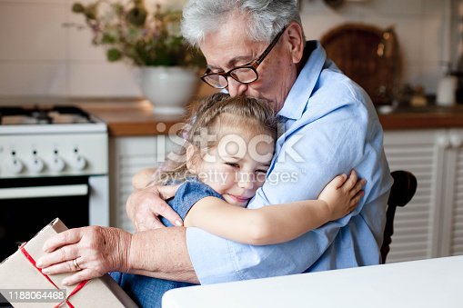 494086690istockphoto Grandmother congratulates child with gift box. Kid and senior woman are hugging 1188064468