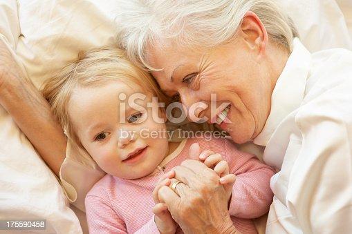 istock Grandmother Cuddling Granddaughter In Bed 175590458