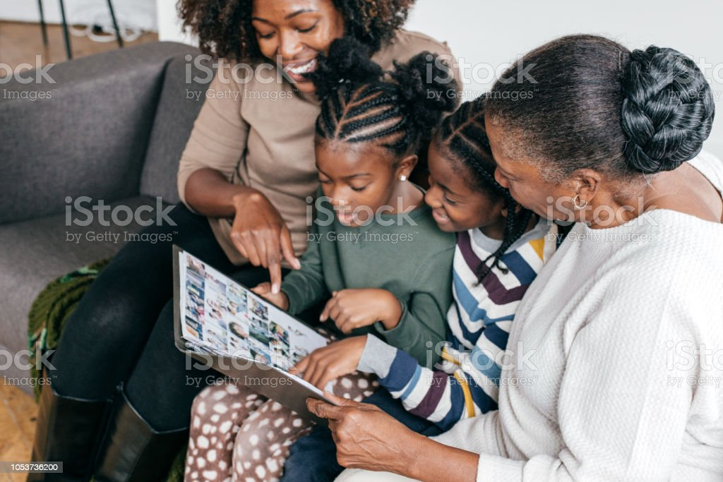 Grandmother, daughter and grandkids looking at photo album stock photo