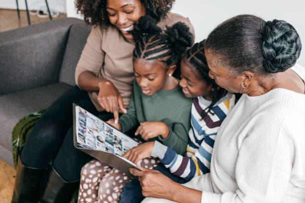 Grandmother, daughter and grandkids looking at photo album Mother grandmother and grandchildren album stock pictures, royalty-free photos & images