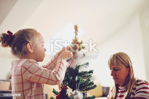 Grandma with granddaughter decorates Christmas tree in the living room with roof window.they put decorations on a tree.