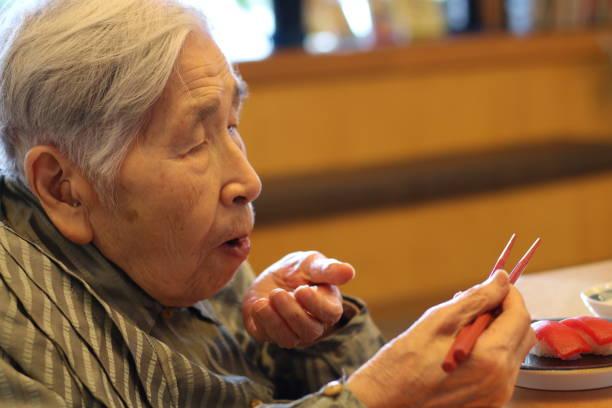 祖母がお寿司を食べて - 高齢者介護 ストックフォトと画像