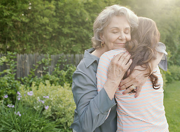grandmother embracing adult granddaughter - granddaughter and grandmother stock photos and pictures