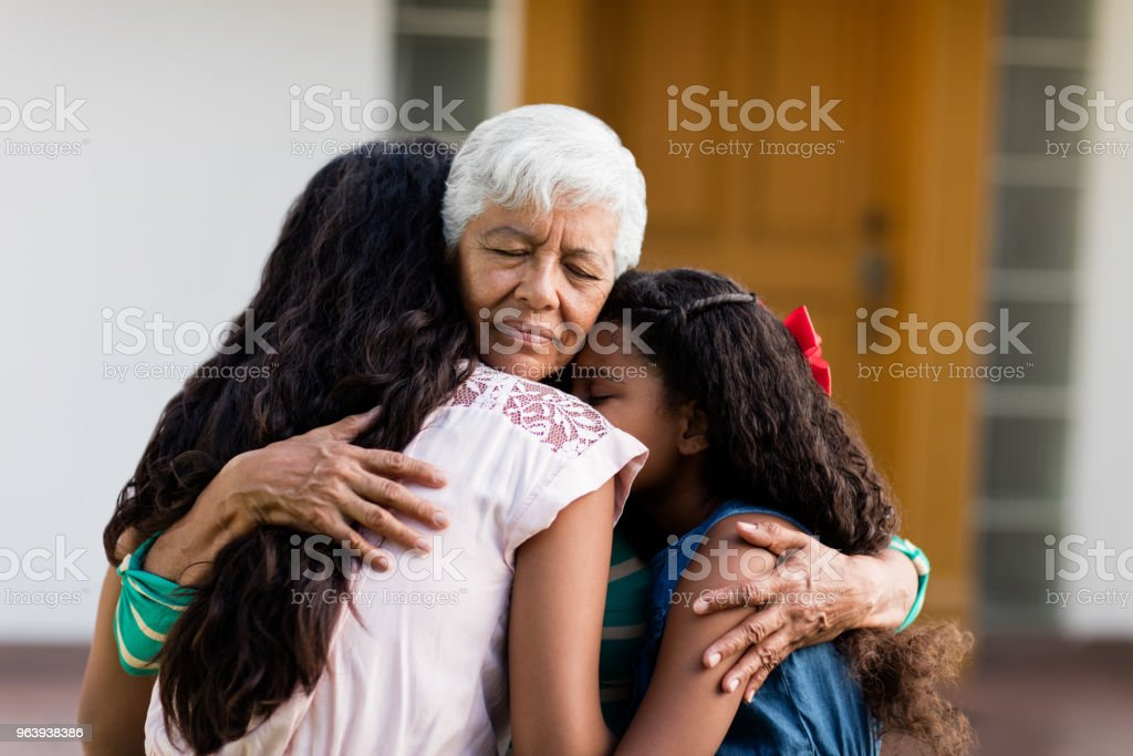 Grandmother embracing her two teen granddaughters outside - Royalty-free 12-13 Years Stock Photo