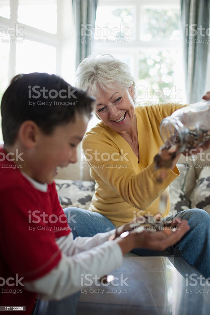 Grandmother emptying jar of coins into grandson's hands royalty-free stock photo