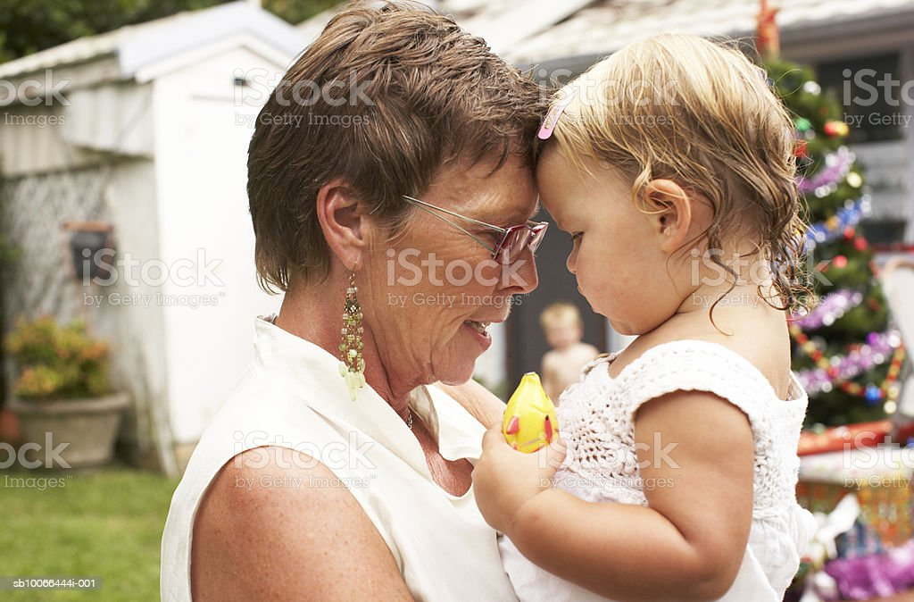 Grandmother face to face with granddaughter (20-24 months) in garden with Christmas tree royalty-free stock photo