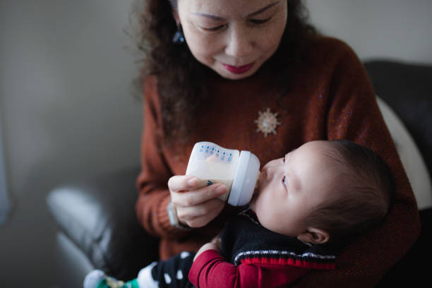 Grandmother feeding a baby boy stock photo