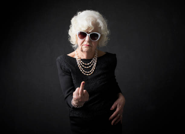 Grandmother flipping people off stock photo