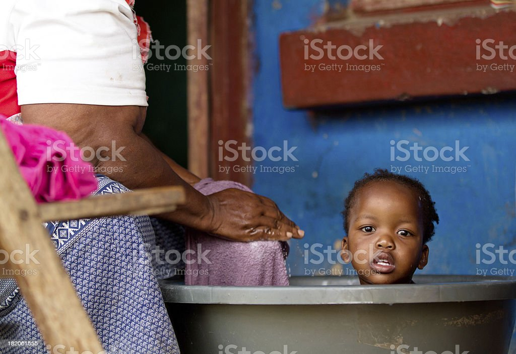 Grandmother gives her granddaughter a bath in rural South Africa stock photo