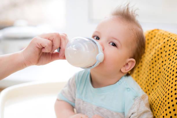 großmutter gibt dem baby ein kompott - innocent saft stock-fotos und bilder