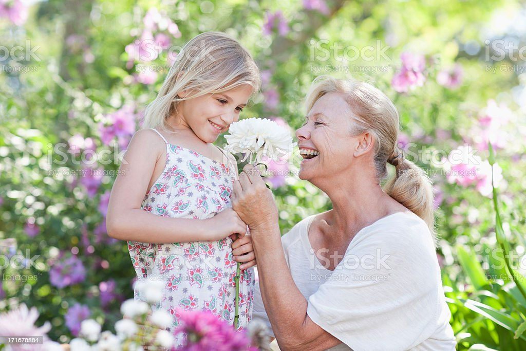 Grandmother giving flower to granddaughter in garden stock photo