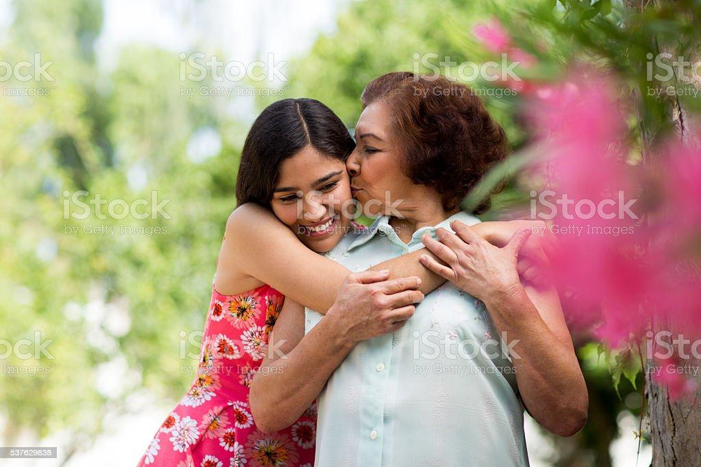Abuela dar nieta un beso - foto de stock