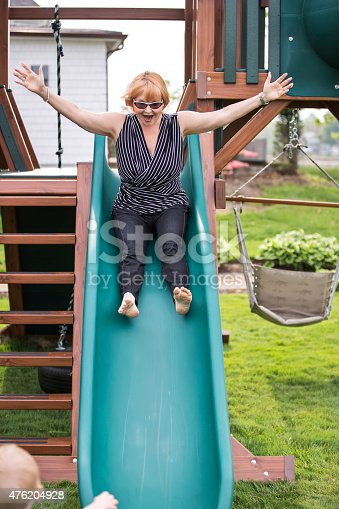 Caucasian grandmother in her fifties with short red hair is going down the slide of her grandchild's outdoor play set in their back yard. Her young grandson is watching her. She is barefoot, has her arms wide open and a big smile. Taken with a Canon 5D Mark 3.rm