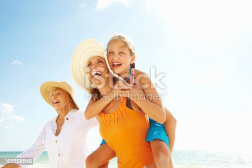 Three generations together - Happy grandmother, granddaughter and daughter enjoying at a beach