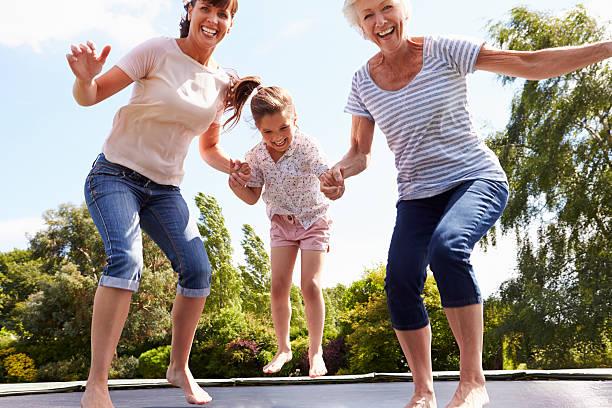 abuela, granddaughter y madre saltando sobre trampolín - trampolín artículos deportivos fotografías e imágenes de stock