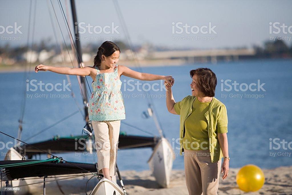 Grandmother helping girl walk on catamaran royalty-free stock photo