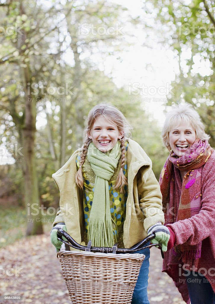 Grandmother helping granddaughter ride bicycle royalty-free stock photo