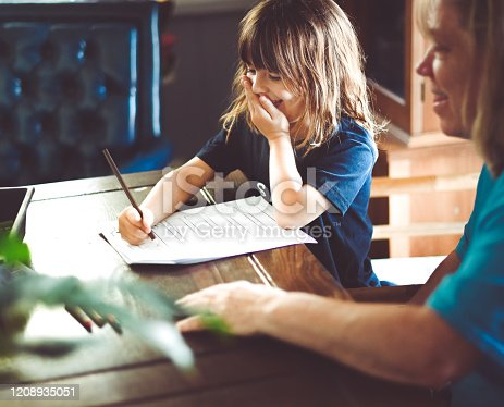 Cute little 5 year old girl does her homework at home at the kitchen table with help from her grandmother in her 60's. They are happy and candid, child is working hard but also cute and cheerful with positive emotion. Slice of domestic life with baby boomer grandmother and elementary age granddaughter