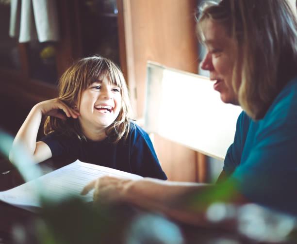 Grandmother helps cute child with kindergarten homework stock photo