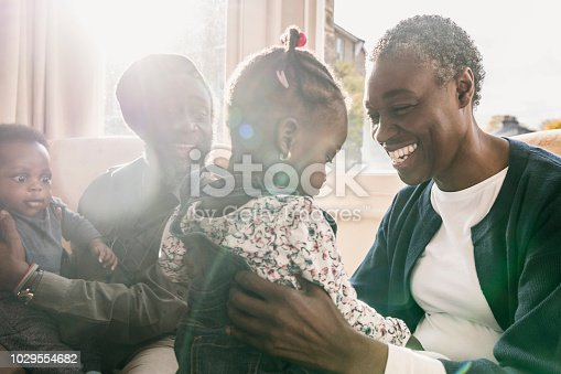 Grandparents with two grandchildren at home by window, close up candid portrait. african ethnicity