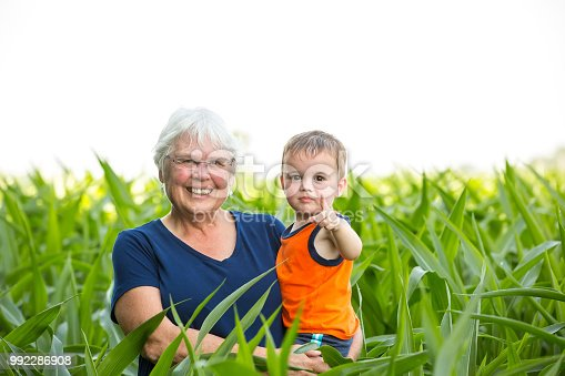 Close-up of a grandmother holding her almost two year old grandson at the edge of a corn field on a summer day. Both are looking at the camera.