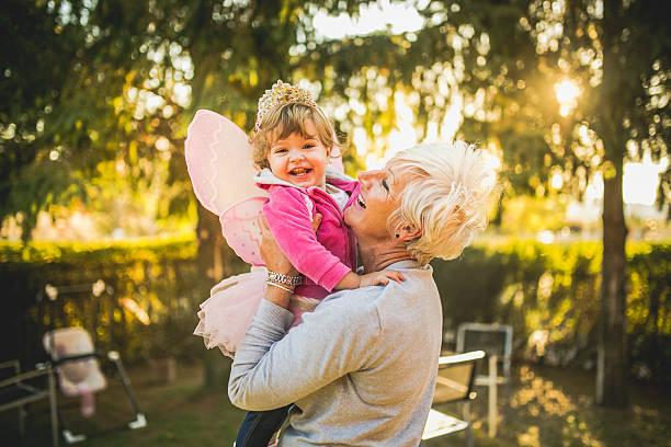 großmutter holding her granddaughter - prinzessinnen tutu stock-fotos und bilder