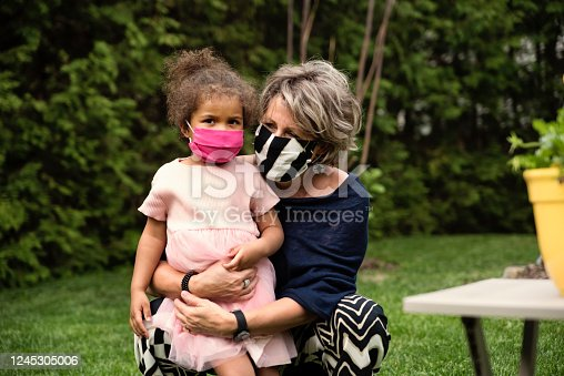 Beautiful senior woman smiling behind her stylish protective mask, holding her 3 year's hold mixed-race granddaughter. Nature in background. Horizontal outdoors waist up shot with copy space.