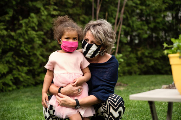 Grandmother holding toddler granddaughter with protective mask. stock photo