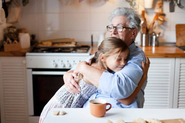 Grandmother hug child girl. Kid and senior woman baking in cozy home kitchen. Happy family stock photo